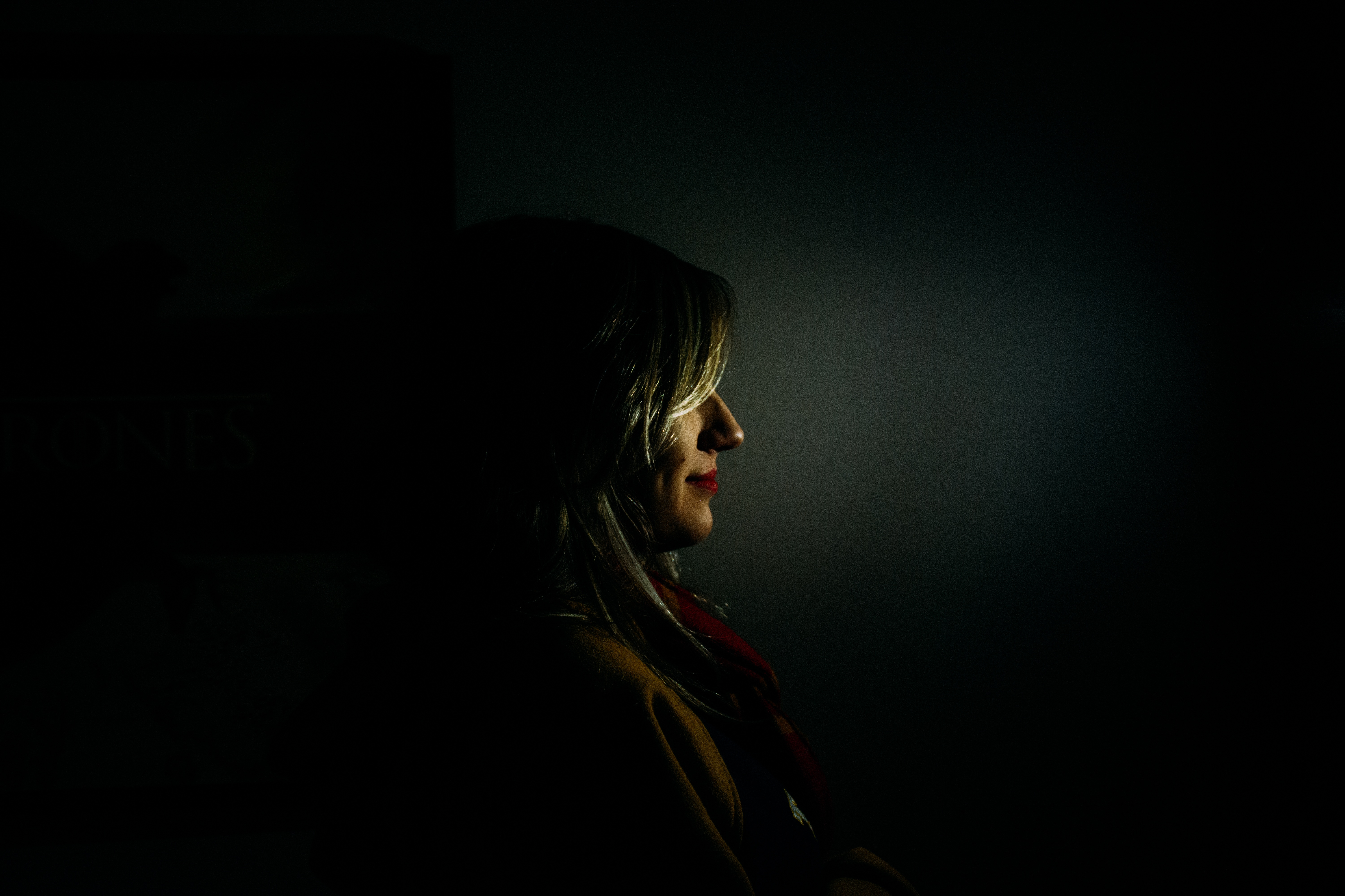 Woman with Half Smile Standing in the Dark
